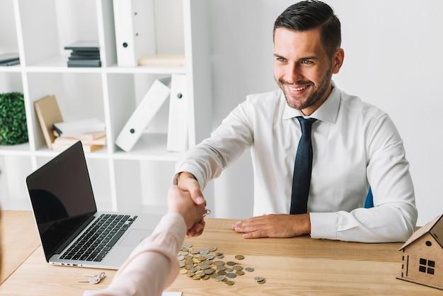Sonriente agente inmobiliario agitando la mano del cliente