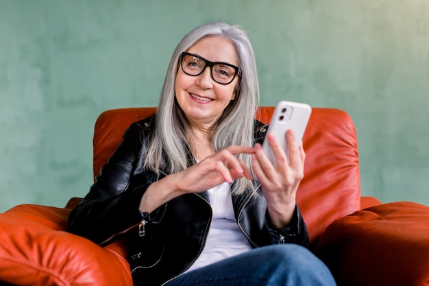 Sonriente agradable dama de pelo gris senior en moda chaqueta de cuero y anteojos, sentado en un gran sillón rojo sobre fondo verde y sosteniendo su teléfono inteligente, mirando a la cámara.