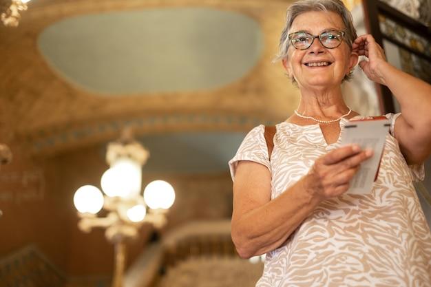 Sonriente anciana entrando en la casa de la música en barcelona, de pie en las escaleras
