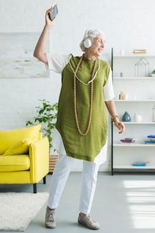 Sonriente anciana escuchando música en auriculares bailando en casa