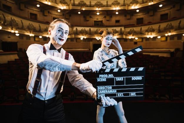Sonriente artista mime hombre sosteniendo claqueta frente a mime femenino en el escenario