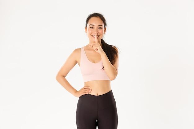 Sonriente atleta femenina bastante asiática, deportista comparte esquema de entrenamiento secreto de cuerpo perfecto, mostrando gesto de silencio, shhh con el dedo sobre los labios.
