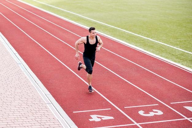 Sonriente atleta masculino corredor en la línea de llegada
