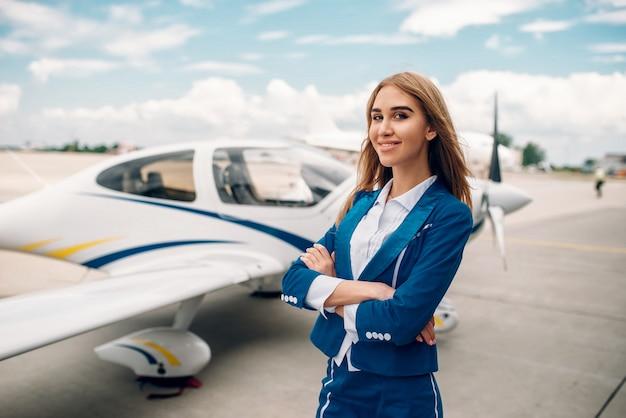 Sonriente azafata en traje contra avión pequeño