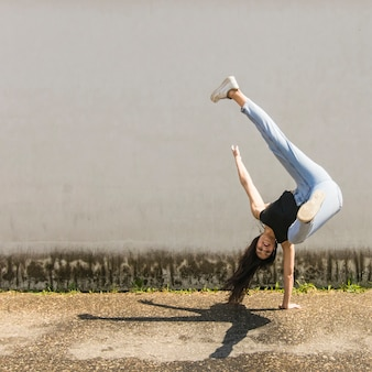 Sonriente bailarina de hip-hop posa frente a la pared gris