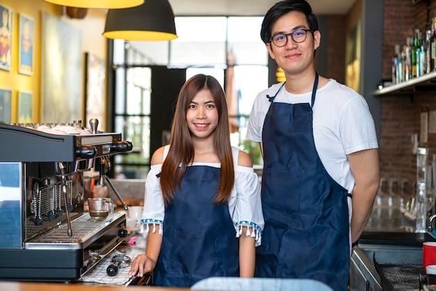 Sonriente barista asiático llevar delantal en barra de bar con cafetera en la cafetería.