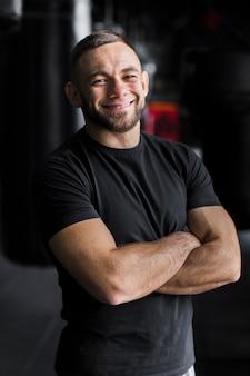 Sonriente boxeador masculino posando en camiseta con los brazos cruzados