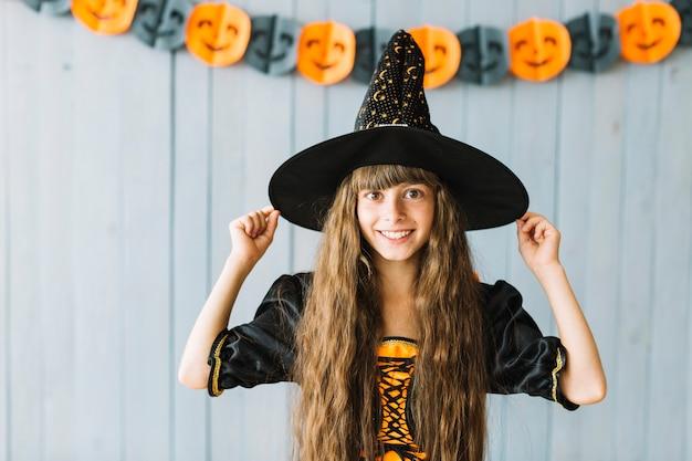 Sonriente brujita en la fiesta de halloween