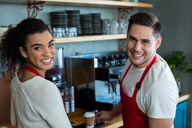 Sonriente camarera y camarero en café