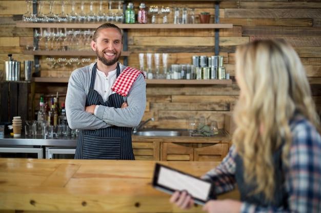 Sonriente camarera y camarero interactuando en mostrador