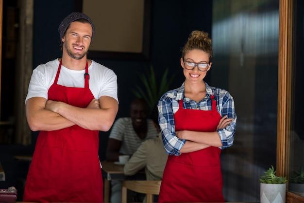 Sonriente camarera y camarero de pie con los brazos cruzados fuera de café