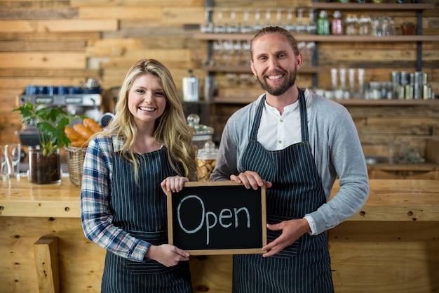 Sonriente camarera y camarero de pie con letrero abierto en café