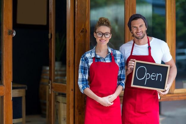 Sonriente camarera y camarero de pie con letrero abierto fuera de café