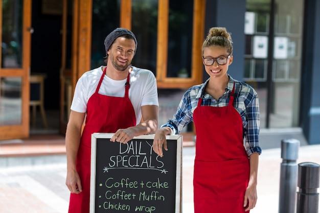 Sonriente camarera y camarero de pie con tablero de menú signo fuera de café