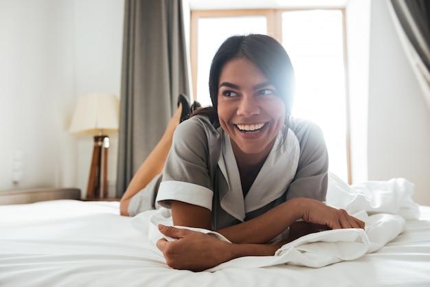 Sonriente camarera del hotel acostada en una cama