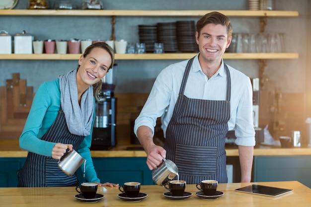 Sonriente camarero y camarera haciendo una taza de café en el mostrador de la cafetería