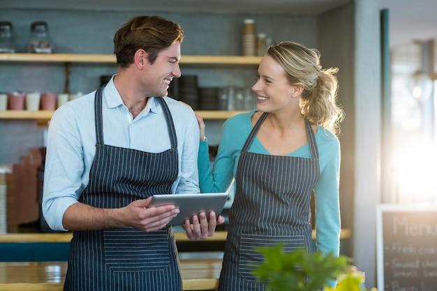 Sonriente camarero y camarera interactuando mientras usa tableta digital