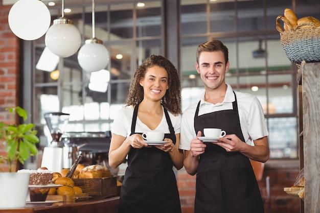 Sonriente camarero y camarera sosteniendo la taza de café