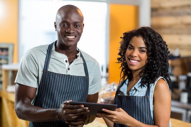 Sonriente camarero y camarera con tableta digital en el mostrador de café