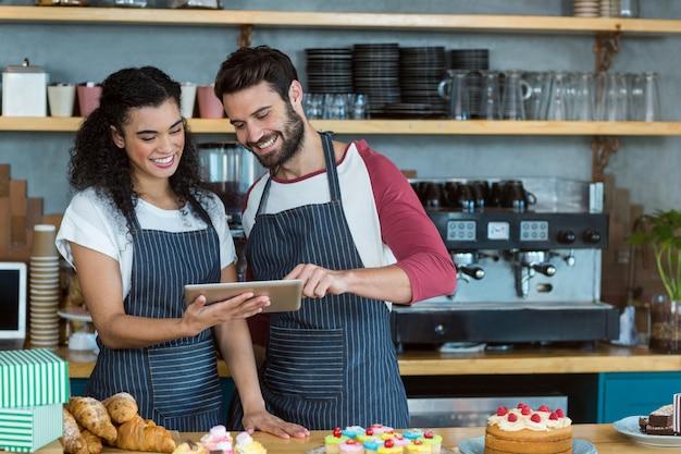 Sonriente camarero y camarera con tableta digital en el mostrador