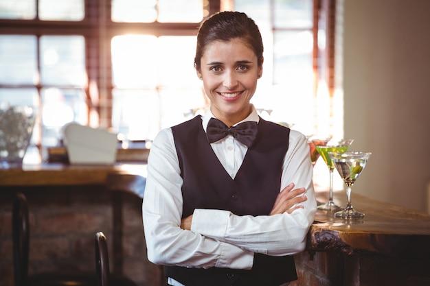 Sonriente camarero femenino de pie con los brazos cruzados