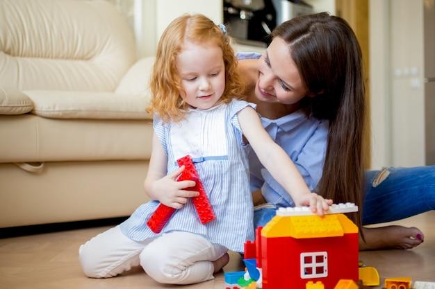 Sonriente casa de la construcción de la hija con la madre joven
