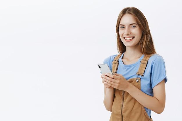 Sonriente chica atractiva que usa el teléfono móvil, envía mensajes de texto o navega por las redes sociales