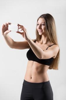 Sonriente chica deportiva tomando selfie, auto-retrato con smartphone