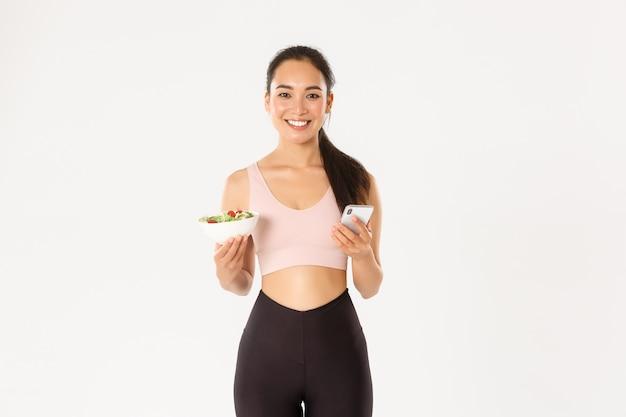 Sonriente chica de fitness asiática delgada en ropa deportiva, sosteniendo una ensalada y un teléfono móvil, usando la aplicación de recordatorio de comer, la aplicación de control de la dieta, controlando las calorías