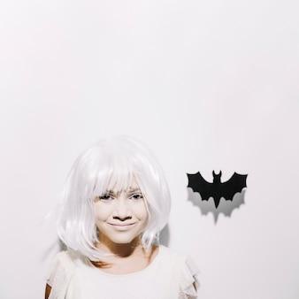 Sonriente chica con murciélago