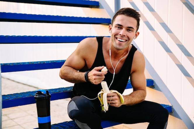 Sonriente chico deportivo en auriculares, comiendo un plátano, después del ejercicio, sentado en las escaleras