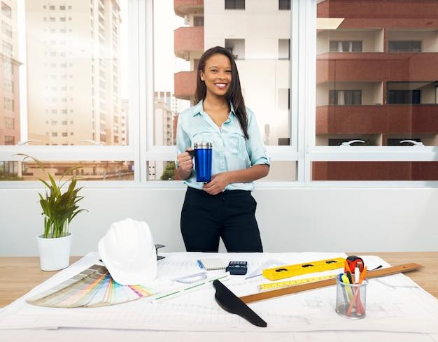 Sonriente dama afroamericana con taza de vacío cerca del plan en la mesa con equipos