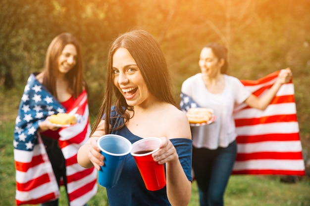Sonriente dama mostrando bebidas
