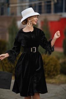 Sonriente dama muy elegante con sombrero blanco y vestido negro caminando por la calle. concepto de calle de moda