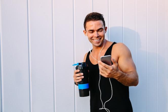 Sonriente deportista atractivo en auriculares viendo una película divertida en teléfono inteligente