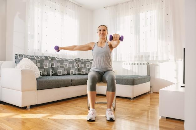 Sonriente deportista musculosa sentada en la silla de su apartamento y haciendo ejercicios de fitness para bíceps con mancuernas.