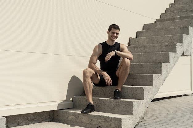 Sonriente deportista sentado en la base de las escaleras ascendentes