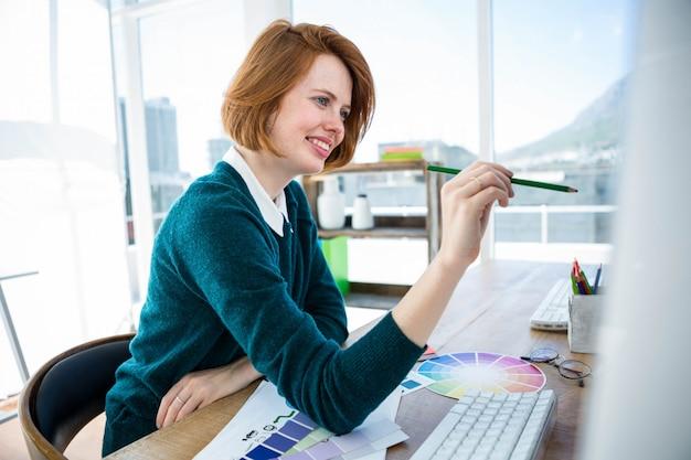 Sonriente diseñador de interiores hipster, en su escritorio, rodeado de cartas de colores