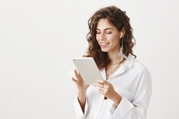 Sonriente empresaria exitosa en auriculares inalámbricos con tableta digital