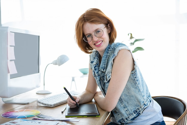 Sonriente empresaria hipster escribiendo en una tableta de dibujo digital en su oficina