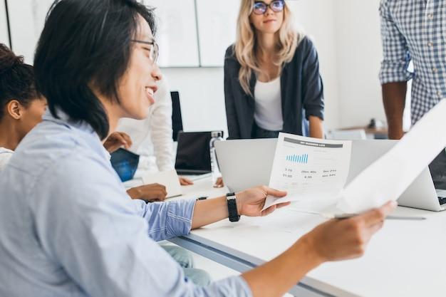 Sonriente empresario asiático analizando infografía en su oficina. retrato de interior de jóvenes especialistas en ti con desarrollador chino en gafas