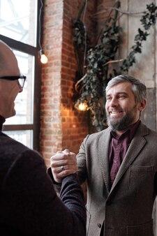 Sonriente empresario barbudo en chaqueta apretón de manos con su colega como símbolo de una relación fuerte