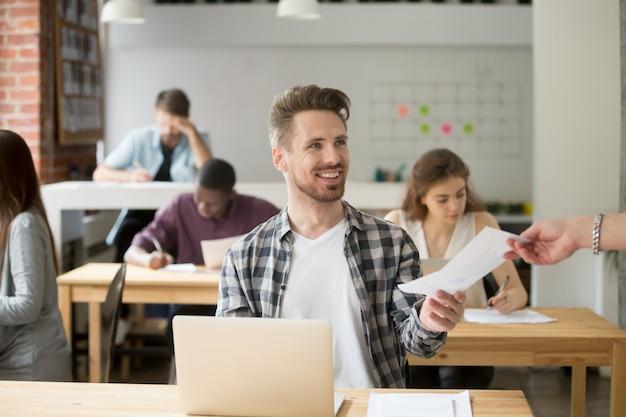 Sonriente empresario guapo dando documento financiero a compañero de trabajo.