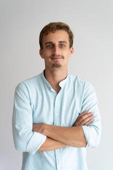 Sonriente empresario masculino con barba y bigote cruzando los brazos en el pecho