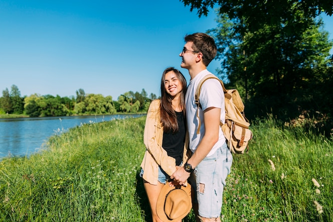 Sonriente encantadora joven pareja de pie en la hierba verde cerca del lago