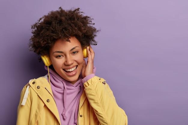 Sonriente enérgica mujer afroamericana hipster
