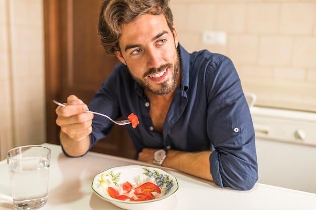 Sonriente ensalada hombre comiendo con un tenedor en el cuenco