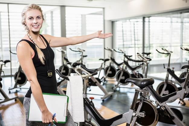 Sonriente entrenador femenino mostrando el gimnasio en la cámara