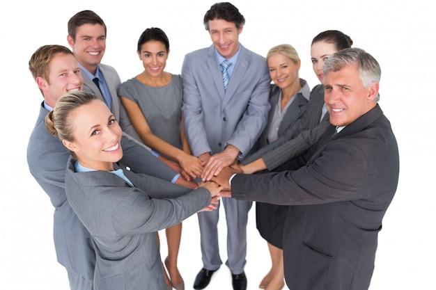 Sonriente equipo de negocios de pie en círculo manos juntas