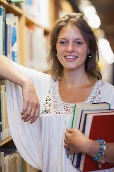 Sonriente estudiante de pie en la biblioteca